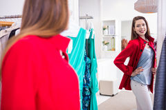 Brunette trying on a red coat royalty free stock photography