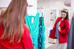 Brunette trying on a red coat Stock Image
