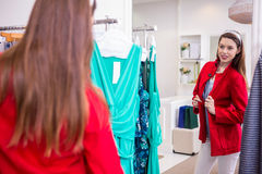 Brunette trying on a red coat Royalty Free Stock Images