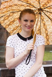 Brunette with snake pattern umbrella 4. A beautiful young woman with long brown hair wearing a black-white shirt with short sleeves and carrying a snake Royalty Free Stock Photo