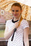 Brunette with snake pattern umbrella 1. A beautiful young woman with long brown hair wearing a black-white shirt with short sleeves and carrying a snake Stock Image