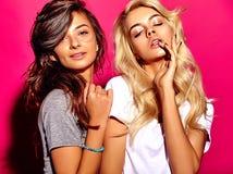 Brunette und blonde Modelle in der zufälligen Kleidung des Sommers auf buntem rosa Hintergrund Stockbilder