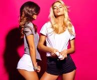 Brunette und blonde Modelle in der zufälligen Kleidung des Sommers auf buntem rosa Hintergrund Stockfotos