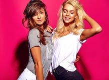 Brunette und blonde Modelle in der zufälligen Kleidung des Sommers auf buntem rosa Hintergrund Lizenzfreies Stockfoto