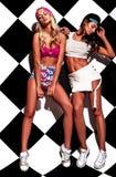 Brunette und blonde Modelle im rnb reden die Kleidung an, die nahe Schachwand aufwirft Lizenzfreies Stockfoto