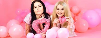 Brunette und blonde nette Frauen in den rosa Pyjamas, die auf Kamera mit rosa Herzen während Lage nahe Luftballonen am Schlummer  Stockfotografie