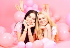 Brunette und blonde nette Frauen in den rosa Pyjamas, die auf Kamera während Lage nahe Luftballonen an der Pyjamaparty über Rosa  Lizenzfreies Stockbild