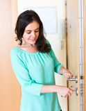 Brunette unlocking outer door Royalty Free Stock Images