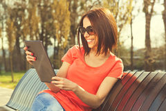 Brunette using digital tablet Royalty Free Stock Photos