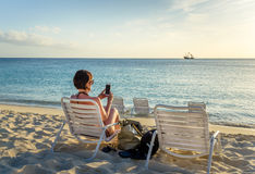 Brunette Using her Mobile Phone on the Beach Royalty Free Stock Photo