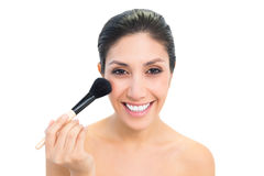 Brunette using a powder brush and smiling Stock Photo