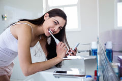 Brunette using smartphone while brushing teeth Stock Images