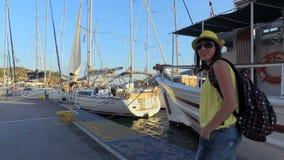 Brunette van het toeristen het mooie, jonge meisje in zonnebril in een gele T-shirt, jeans, een gele hoed en met gekleurd stock footage