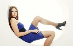 Brunette in vestito blu che si siede in un cerchio immagine stock libera da diritti