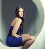 Brunette in vestito blu che si siede in un cerchio fotografie stock libere da diritti