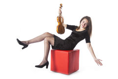 Brunette with violin has fun on red stool in studio Stock Photos
