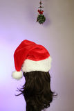 Brunette waiting for kiss. Waiting under mistletoe for a Christmas kiss is a brunette in a santa hat Royalty Free Stock Images