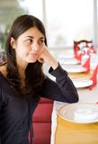 Brunette waiting in a restaurant. Brunette girl waiting at the table in a restaurant with an empty plate in front of her Royalty Free Stock Photo