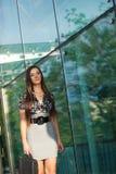 Brunette walking along glass wall Stock Photo