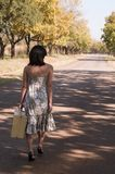 Brunette walking with suitcase Royalty Free Stock Images