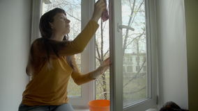 The brunette washes the window on a spring day. stock video footage