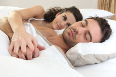 Brunette watching boyfriend sleep Stock Image