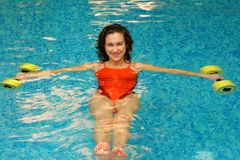 Brunette in water with dumbbels Stock Images