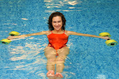 Brunette in water met dumbbels stock foto
