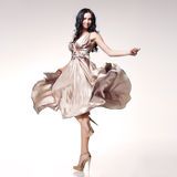 Brunette in waving dress. Young beautiful caucasian brunette in gorgeous dress, motion shot Royalty Free Stock Photo