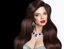Brunette. wavy hair and jewelry, red lips makeup, long healthy e Royalty Free Stock Photos