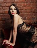 Brunette wearing black lingerie posing on chair Royalty Free Stock Photography