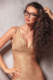 Brunette wearing glasses poses while fixing her hair Royalty Free Stock Photography