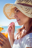 Brunette wearing straw hat and drinking a cocktail Royalty Free Stock Photo