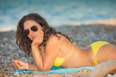 Brunette wearing yellow bikini Stock Images