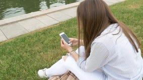 Brunette weißes Hemd, sitzend auf dem grünen Gras mit ihrem Smartphone, der sms sendet stock video footage