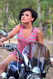 Brunette at the wheel of the bike, portrait. Brunette with short hair at the wheel of the bike Royalty Free Stock Photo