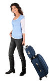Brunette wheeling luggage. By handle Stock Images