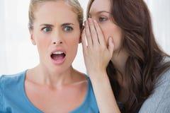Brunette whispering secret to her friend Royalty Free Stock Images