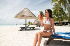 A brunette in a white bathing suit sits on a lounger and drinks a Pina Colada cocktail in a pineapple.  stock image