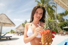 A brunette in a white bathing suit sits on a lounger with a Pina Colada cocktail in a pineapple.  royalty free stock photo
