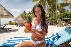 A brunette in a white bathing suit sits on a lounger with a Pina Colada cocktail in a pineapple.  stock image