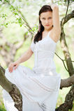 Brunette in white dress sitting Stock Images
