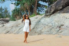 Brunette in white dress walking along the beach Royalty Free Stock Photography