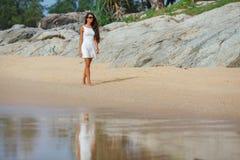 Brunette in white dress walking along the beach Royalty Free Stock Photo