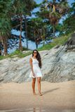 Brunette in white dress walking along the beach Royalty Free Stock Images