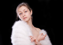 The brunette in a white fur coat. On a black background, isolation Royalty Free Stock Photo