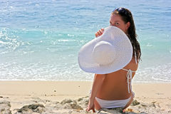 Brunette with white hat on beach Stock Image