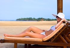 Brunette in white hat on chaise longue Stock Photos