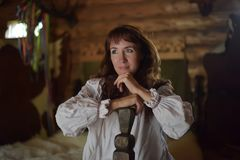 Brunette in white linen old-fashioned shirt with embroidery sits on a medieval bed royalty free stock image