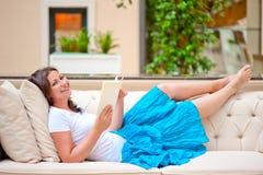 Brunette on white sofa reading a book. Brunette on white sofa reading book Stock Image